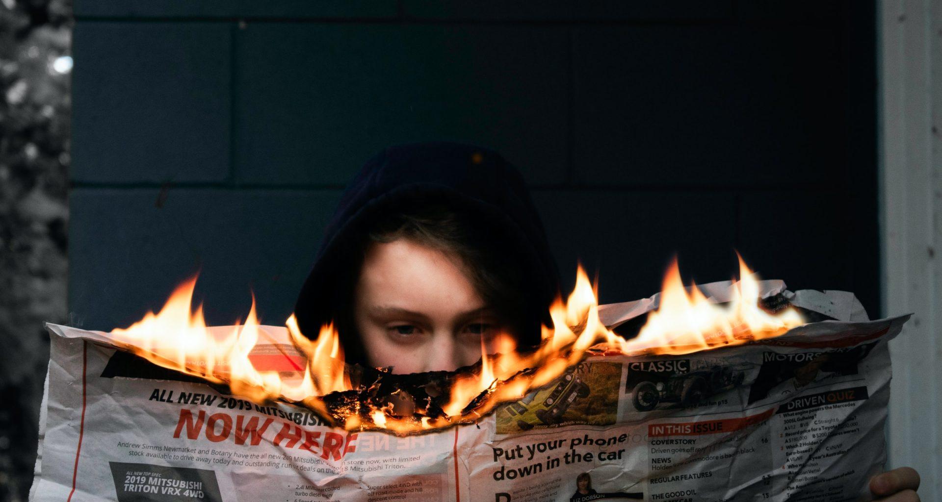 Elinde yanan bir gazete tutan bir kadın.