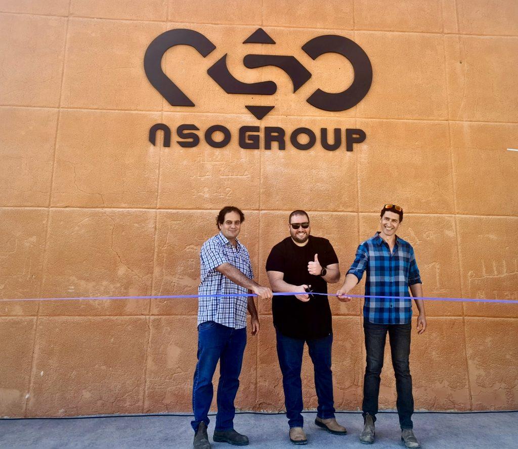 NSO Group'un CEO'su ve bölgede yaşayan iki kişi şirket logosunun olduğu bir duvarın önünde kurdele keserek poz veriyor.