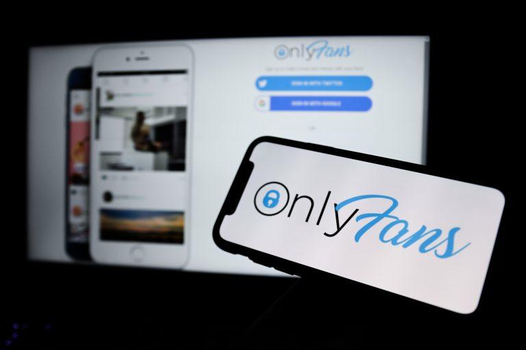 Bilgisayar ekranında OnlyFans'ın ana sayfası, önündeki telefonda OnlyFans'ın logosu görünüyor.